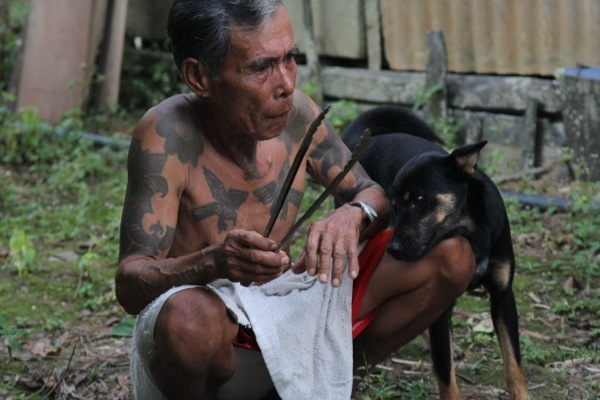 Iban elder with traditional tattoos and dog